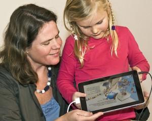 Hier ziet u de iPad met het witte verloopkabeltje en de geluidskabel. Het meisje bedient de iPad, de zaal kijkt mee op een groot scherm.